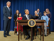 U.S. President Barack Obama, reaches back to comment to a fellow lefty during a press conference at the White House to unveil a package of proposals to reduce gun violence January 16, 2013 in Washington D.C.  Vice President Jo Biden looks on.  Photo Ken Cedeno.