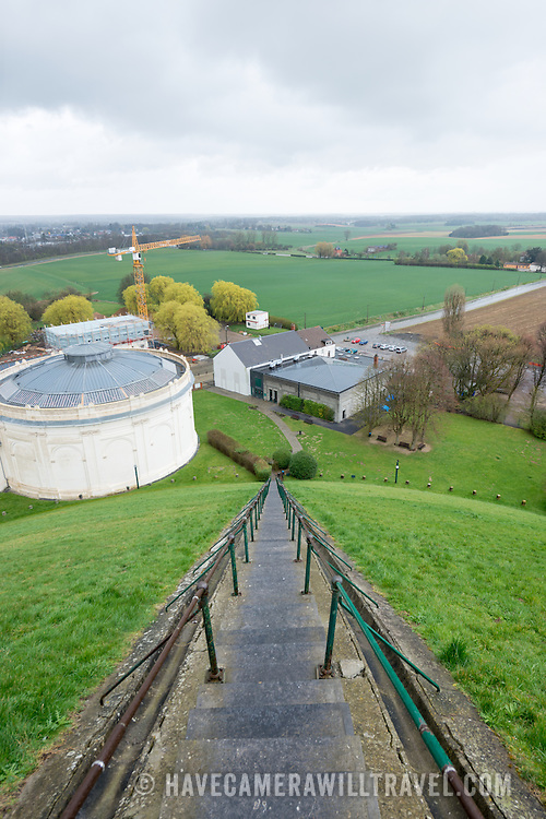 Steps leading to the top of the Lion's Mound (Butte du Lion), an artificial hill built on the battlefield of Waterloo to commemorate the location where William II of the Netherlands was injured during the battle. The hill is situated on a spot along the line where the Allied army under the Duke of Wellington's command took up positions during the Battle of Waterloo. At left of frame, the white cylindrical building houses the Panorama.