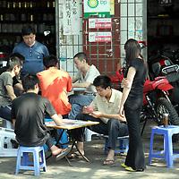 Asia, China, Chongqing. Teens playing card games on the sidewalks.