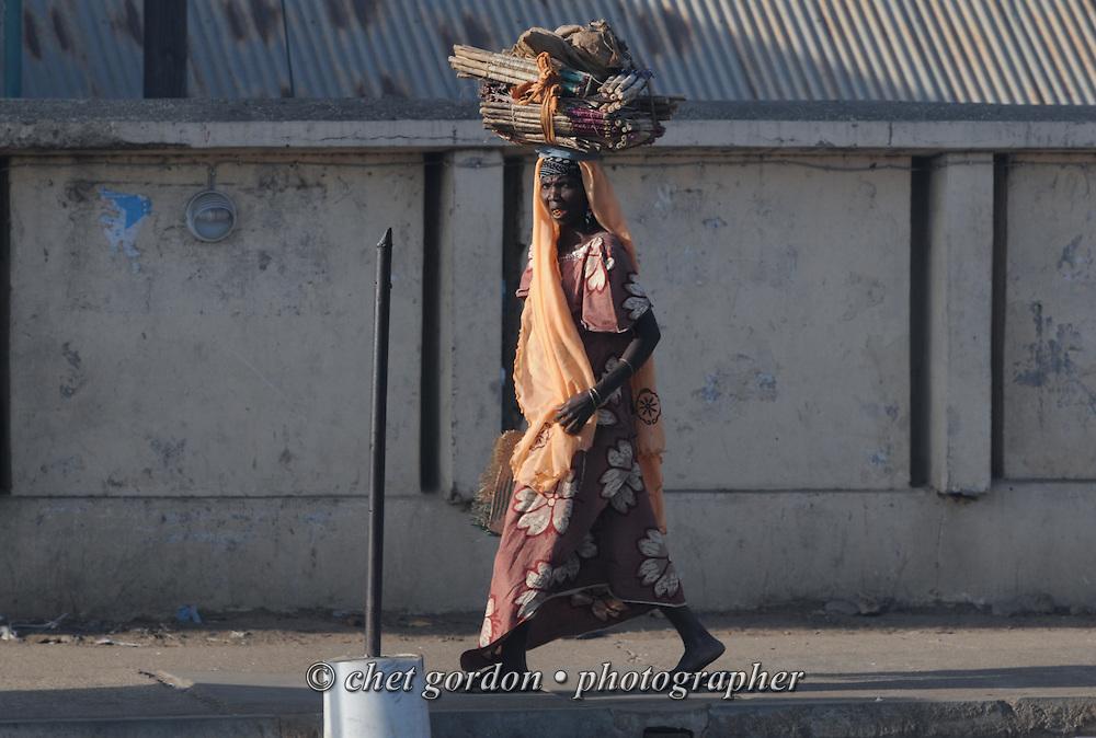 A Nigerian woman walks along Kofar Mata Road in Kano, Nigeria on Wednesday, December 5, 2012.