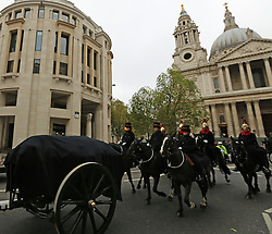 © Licensed to London News Pictures. 30/11/2013. Sacred soil from the battlefields of Flanders has been carried through the streets of London on a gun carriage. The soil arrived yesterday on a Belgian frigate and was loaded on to a gun carriage this morning. The gun carriage was drawn by six colour matched black Irish Draught horses and was taken to Wellington Barracks. Pictured passing St Paul's. Credit : Rob Powell/LNP