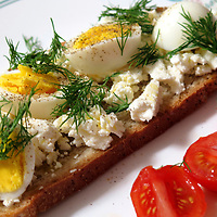 Feta cheese mixed with olive oil over toasted bread, topped with fresh dill and boiled eggs.