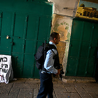 An Israeli police officer patrol next to a sign saying &quot; Here  (sellers) were involved in the murder&quot; outside of closed Palestinian shops  where a stabbing attack took place in Jerusalem's Old City, Sunday, Oct.8, 2015. <br />