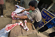 Tam Duong market. Butcher. Butterfly on buffalo leg.