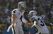 Dec 31, 2017; Carson, CA, USA; Oakland Raiders quarterback Derek Carr (4) and running back DeAndre Washington (33) celebrate after a touchdown in the second quarter against the Los Angeles Chargersduring an NFL football game at StubHub Center.