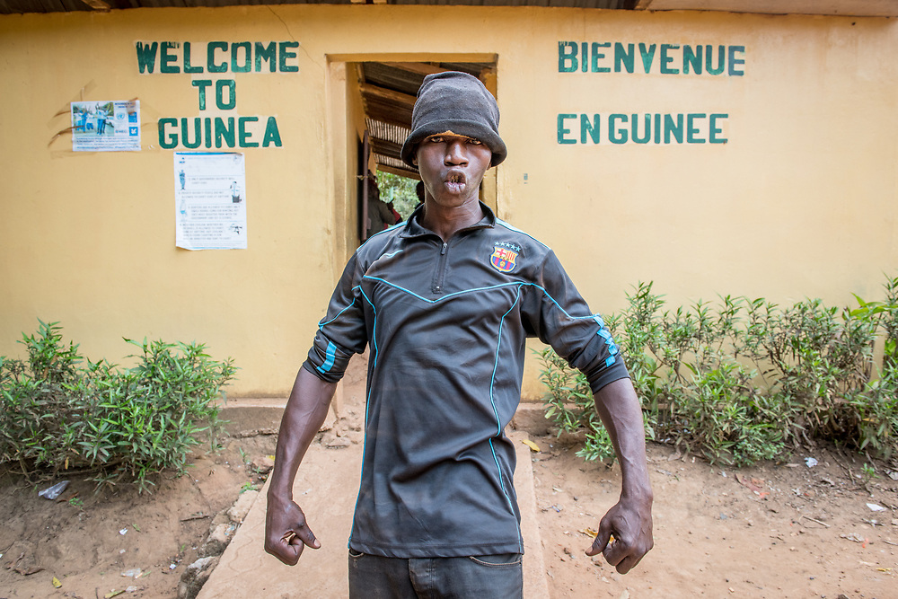 Adult African male stands in powerful stance with closed fists in front of  Republic of Guinea border crossing