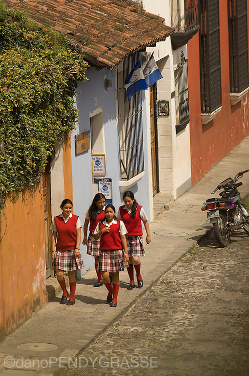 Schoolgirls in uniform walk along the cobbled streets of <br /> Antigua, Guatemala.