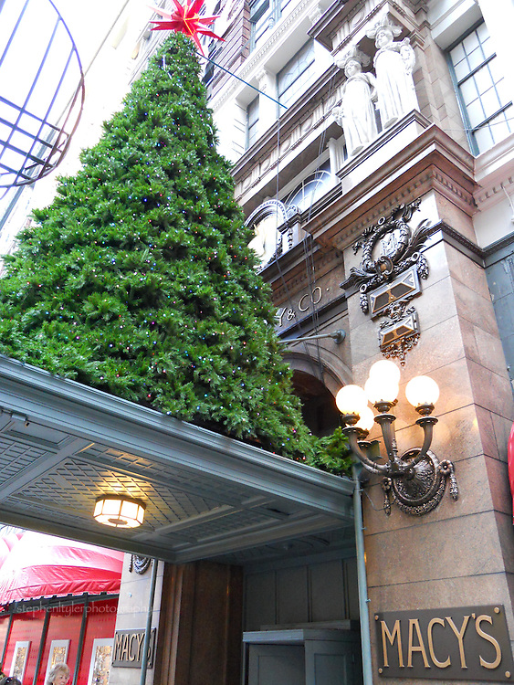 A Christmas tree atop the awning on Macy's Department Store reminds all of the holiday season and the shopping needs to be filled inside.