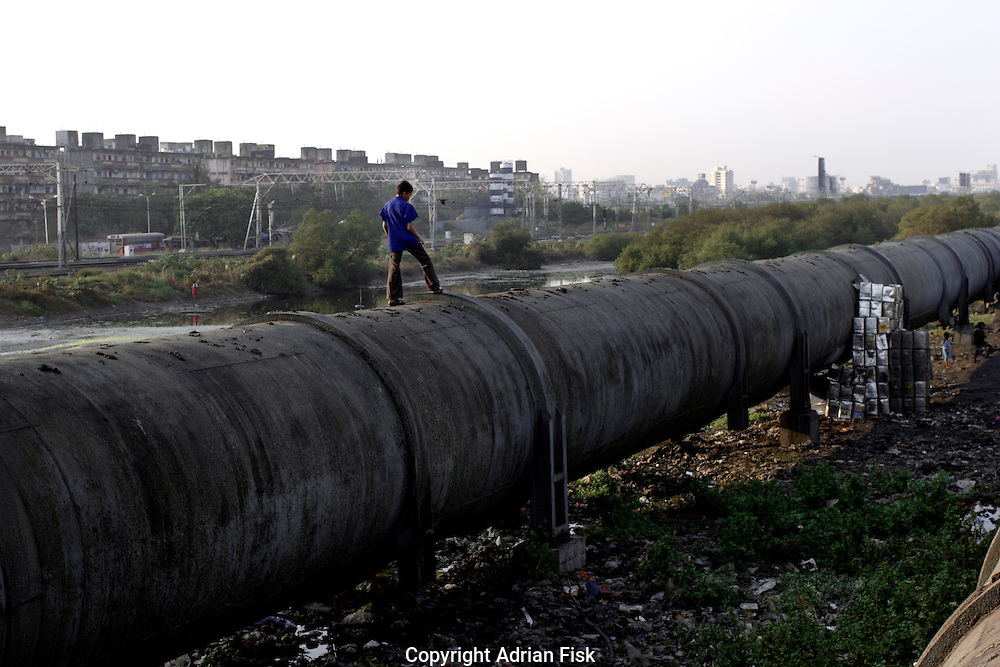 A boy walks along one of the water pipes that passes through Dharavi on 21st Oct 2006. The pipes carry Bombays water supply but for the resisdents of Dharavi access to clean drinking water is rare.