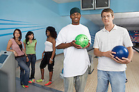 Group of friends at bowling alley some holding balls portrait
