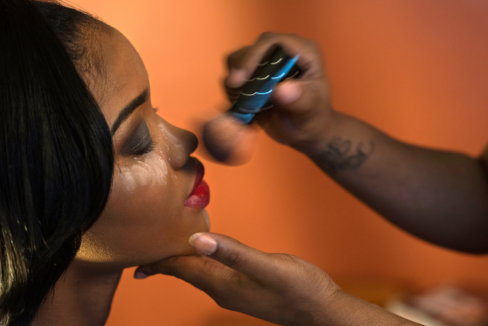 Tyneisha Wilder sits patiently as powder is applied to her face during prom preparations at her foster mother's home in Wilkinsburg. Tyneisha was diagnosed just last year with Intellectual Developmental Disability