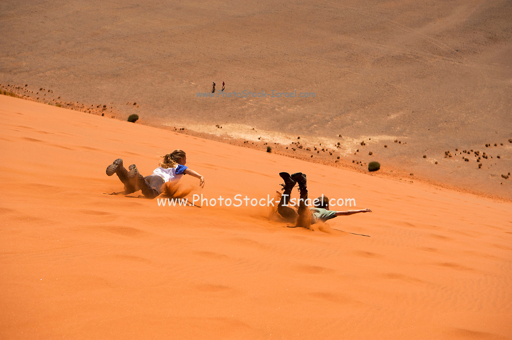 Hikers dune surfing down a sand dune at Sossusvlei, Namib-Naukluft National Park, Namibia.