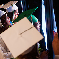 051613       Cable Hoover<br /> <br /> Gallup Catholic High School seniors Correna Joe, left, Alexis Jenson and Gary King peek out of the curtains of the ready room before their graduation ceremony at El Morro Theater Thursday.