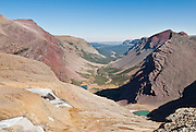 """From Siyeh Pass, see glaciers and orange and purple mountains at the headwaters of Boulder Creek Canyon, in Glacier National Park, Montana, USA (September 2007 photo). Hike Siyeh Pass, a gorgeous traverse of 10.3 miles (2300 feet up, 3500 feet down) starting at Siyeh Bend, through Preston Park, and finishing down beautiful Baring Creek Valley. Since 1932, Canada and USA have shared Waterton-Glacier International Peace Park, which UNESCO declared a World Heritage Site (1995) containing two Biosphere Reserves (1976). Rocks in the park are primarily sedimentary layers deposited in shallow seas over 1.6 billion to 800 million years ago. During the tectonic formation of the Rocky Mountains 170 million years ago, the Lewis Overthrust displaced these old rocks over newer Cretaceous age rocks. Glaciers carved spectacular U-shaped valleys and pyramidal peaks as recently as the Last Glacial Maximum (the last """"Ice Age"""" 25,000 to 13,000 years ago). Of the 150 glaciers existing in the mid 1800s, only 25 active glaciers remain in the park as of 2010, and all may disappear by 2020, say climate scientists."""