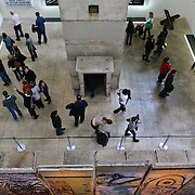 Taken from above, tourists explore the Berlin Wall exhibit at the Newseum in Washington DC. Featuring a guard tower and sections of the original Berlin Wall, the Newseum's exhibit is one of the largest on the subject outside Berlin. The Newseum is a 7-story, privately funded museum dedicated to journalism and news. It opened at its current location on Pennsylvania Avenue in April 2008.