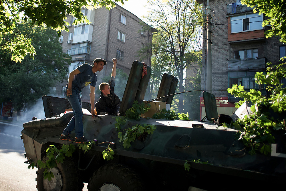 Separatists celebrate after they repaired the engine of an APC, abandoned by the Ukrainian army in Mariupol.