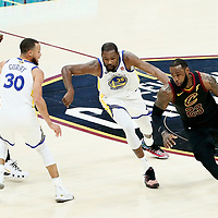 CLEVELAND, OH - JUN 3: LeBron James #23 of the Cleveland Cavaliers drives past Kevin Durant #35 of the Golden State Warriors next to Stephen Curry #30 of the Golden State Warriors and Kevon Looney #5 of the Golden State Warriors in Game Three of the 2018 NBA Finals won 110-102 by the Golden State Warriors over the Cleveland Cavaliers at the Quicken Loans Arena on June 6, 2018 in Cleveland, Ohio. NOTE TO USER: User expressly acknowledges and agrees that, by downloading and or using this photograph, User is consenting to the terms and conditions of the Getty Images License Agreement. Mandatory Copyright Notice: Copyright 2018 NBAE (Photo by Chris Elise/NBAE via Getty Images)