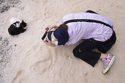 Taketomi-jima. Tourist photographing the famous cats at Gaiji-hama (Star Sand Beach).