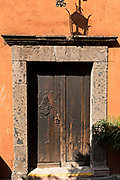 An old wooden doorway with stone surround on a historic house in San Miguel de Allende, Mexico. San Miguel de Allende has more than 2,000 old wooden colonial doors dating from the 1800's making the city unique in Mexico.