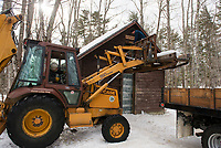 Time honored traditions with a little modern convenience as Bill Sharkey operates the fork lift while Martin Carney slides ice blocks into Rockywald's Ice House on Thursday afternoon.  (Karen Bobotas/for the Laconia Daily Sun)