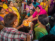 31 AUGUST 2014 - SARIKA, NAKHON NAYOK, THAILAND: People receive blessing during the Ganesh festival at Shri Utthayan Ganesha Temple in Sarika, Nakhon Nayok. Ganesh Chaturthi, also known as Vinayaka Chaturthi, is a Hindu festival dedicated to Lord Ganesh. It is a 10-day festival marking the birthday of Ganesh, who is widely worshiped for his auspicious beginnings. Ganesh is the patron of arts and sciences, the deity of intellect and wisdom -- identified by his elephant head. The holiday is celebrated for 10 days, in 2014, most Hindu temples will submerge their Ganesh shrines and deities on September 7. Wat Utthaya Ganesh in Nakhon Nayok province, is a Buddhist temple that venerates Ganesh, who is popular with Thai Buddhists. The temple draws both Buddhists and Hindus and celebrates the Ganesh holiday a week ahead of most other places.    PHOTO BY JACK KURTZ