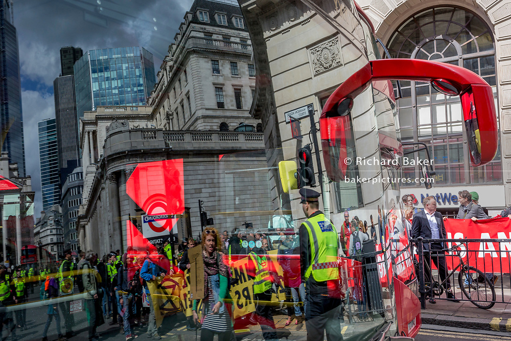 Reflected in the windscreen of a stationary bus, environmental activists protest outside the Bak of England in the City of London on the 11th and final day of protests, road-blockages and arrests across London by the climate change campaign Extinction Rebellion, on 25th April 2019, in London, England.