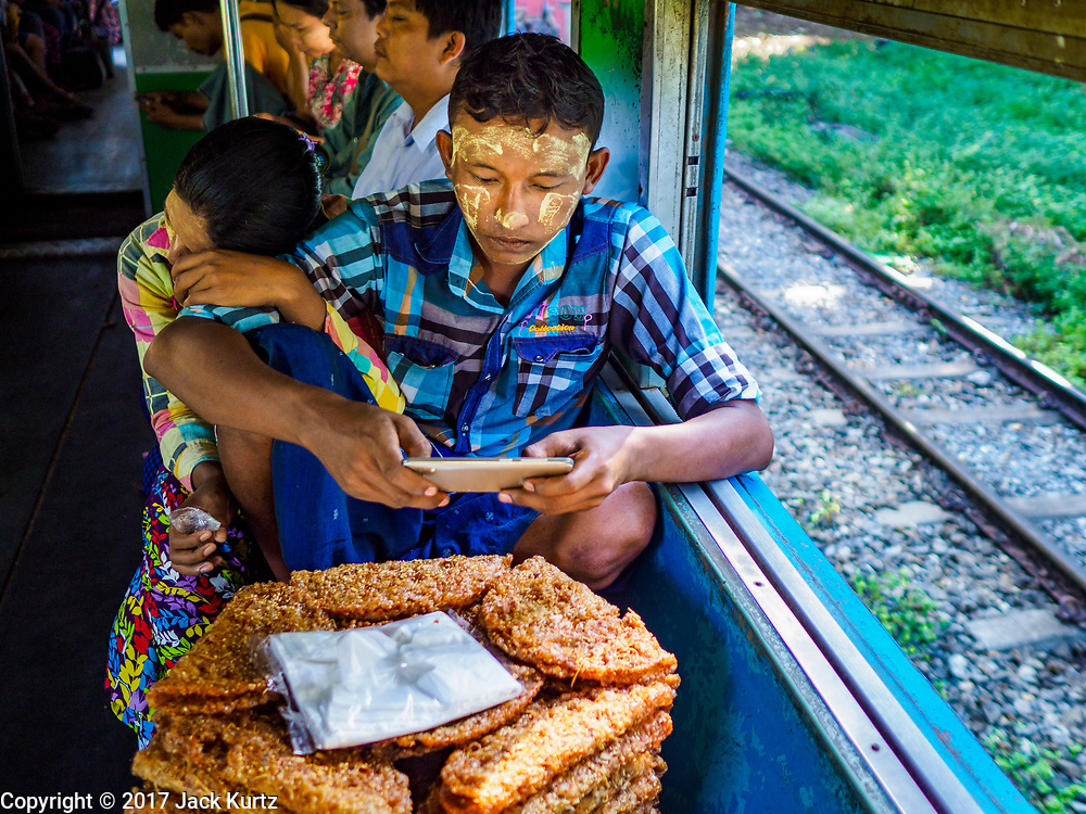 25 NOVEMBER 2017 - YANGON, MYANMAR: A snack vendor traveling with his wife checks his smart phone on the Yangon Circular Train. The Yangon Circular Train is a 45.9-kilometre (28.5 mi) 39-station two track loop system connects satellite towns and suburban areas to downtown. The train was built during the British colonial period, the second track was built in 1954. Trains currently run both directions (clockwise and counter-clockwise) around the city. The trains are the least expensive way to get across Yangon and they are very popular with Yangon's working class. About 100,000 people ride the train every day. A a ticket costs 200 Kyat (about .17¢ US) for the entire 28.5 mile loop.    PHOTO BY JACK KURTZ