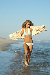Young girl walking playfully along the beach in a bikini and sweater