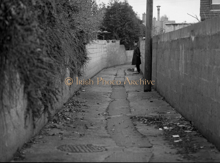 Philip Cairns Disappearance..1986..30.10.1986..10.30.1986..30th October 1986..On 23rd October 1986,schoolboy,Philip Cairns disappeared. He was returning to school after lunch but never arrived. A week later his schoolbag was found in an alleyway close to his home in Rathfarnham. It was suspected that his abductor left the bag in order to dispose of evidence and to confuse the Garda investigation. Rumour was rife that Philip had fallen into the clutches of a paedophile ring who may have killed him to cover their tracks..Up to 2012 the disappearance of philip Cairns still remains a mystery. today he would be aged about forty...A member of the Gardai pictured standing by the schoolbag as it awaits forensic inspection.