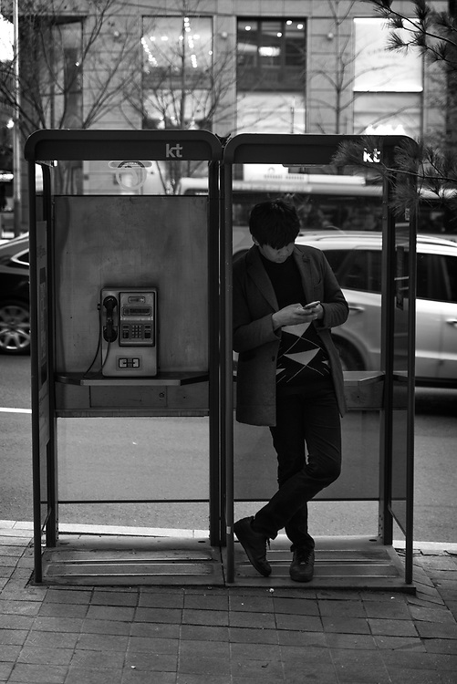 A pedestrian stops inside a phone booth to receive a text message. Gangnam, Seoul, South Korea