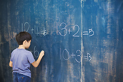 August 16, 2016 - A group of children in school. A boy writing in chalk on a chalkboard. (Credit Image: © Mint Images via ZUMA Wire)