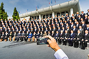 21 AUGUST 2014 - BANGKOK, THAILAND:     A legislative staffer uses an iPhone to take a picture of the Thai National Legislative Assembly (NLA) during their group photo Thursday at the parliament in Bangkok before selecting a new Prime Minster. The NLA was hand selected by the Thai junta, formally called the National Council for Peace and Order (NCPO), and is supposed to guide Thailand back to civilian rule after a military coup overthrew the elected government in May. The NLA unanimously selected General Prayuth Chan-ocha, commander of the Thai Armed Forces and leader of the coup in May that deposed the elected civilian government, as Prime Minister. Prayuth is Thailand's 29th Prime Minister since the 1932 coup that created Thailand's constitutional monarchy.    PHOTO BY JACK KURTZ