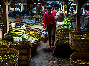 04 AUGUST 2017 - PAYANGAN, BALI, INDONESIA: A shopper walks through the local market in Payangan, about 45 minutes from Ubud. Bali's local markets are open on an every three day rotating schedule because venders travel from town to town. Before modern refrigeration and convenience stores became common place on Bali, markets were thriving community gatherings. Fewer people shop at markets now as more and more consumers go to convenience stores and more families have refrigerators.      PHOTO BY JACK KURTZ