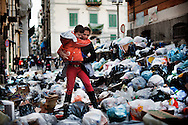 ITALY, NAPLES : A mother carrying her son walks through uncollected garbage downtown Naples in the historic Spanish district on November 22, 2010. Naples latest garbage emergency is getting worst day after day and piles of garbage are seen all over the italian souther city. AFP PHOTO / ROBERTO SALOMONE