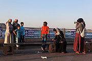 Young Turkish woman eating while a family of Turkish tourists have their photograph taken at the Eminonu quayside, Istanbul, Marmara, Turkey. Eminonu is on the South bank of the Golden Horn at the Southern end of the Galata bridge. Picture by Manuel Cohen