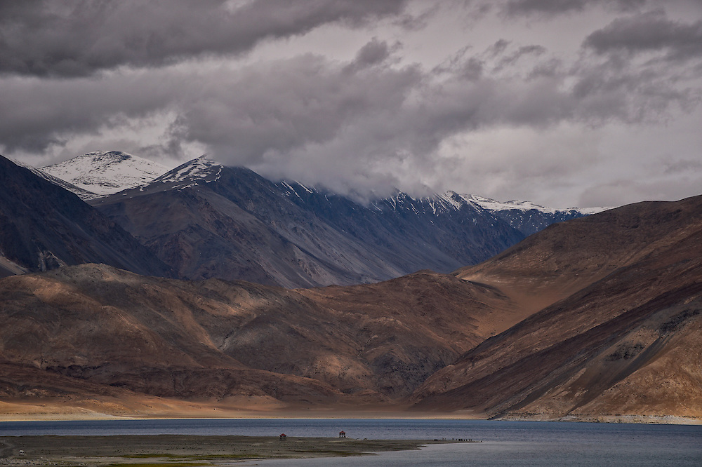 Mountains, clouds, lake and the little human figures relaxing in the perfect rural rhythm of their surroundings. <br />
