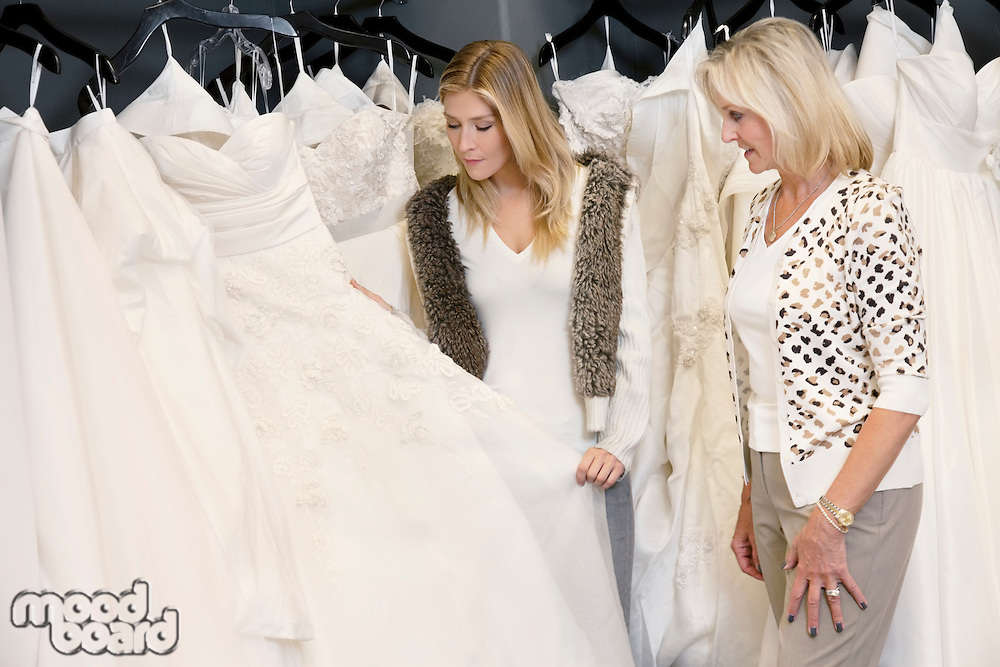 Young woman with senior mother selecting wedding dress in bridal store