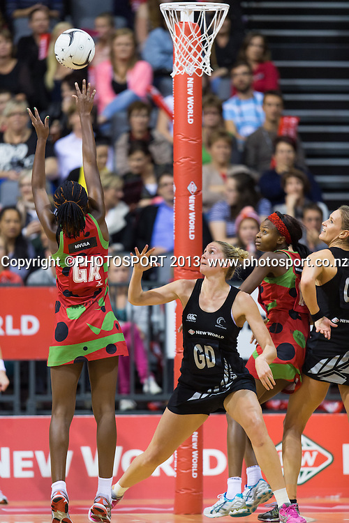 Malawi Queens GA Jessie Mazengera shoots with Silver Ferns GD, captain Casey Kopua looking on during the New World Netball Series - Silver Ferns v Malawi, won by NZ 72-39 at Claudelands Arena, Hamilton, New Zealand, Thursday 31 October 2013. Photo: Stephen Barker/Photosport.co.nz