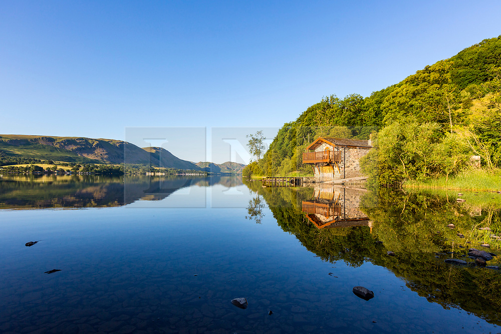 © Licensed to London News Pictures. 29/06/2018. Pooley Bridge UK. The Duke of Portland boat house near Pooley Bridge reflect's in to the calm water of Ullswater lake in Cumbria this morning. Photo credit: Andrew McCaren/LNP