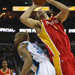 Jan 02, 2010; New Orleans, LA, USA; Houston Rockets forward Luis Scola (4) draws a foul as he shoots over New Orleans Hornets forward David West (30) during the first quarter at the New Orleans Arena. Mandatory Credit: Derick E. Hingle-US PRESSWIRE