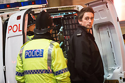 """© Licensed to London News Pictures . 19/12/2014 . Manchester , UK . A man is detained in the back of a police van on Dantzic Street . """" Mad Friday """" revellers out in the rain and cold in Manchester . Mad Friday is typically the busiest day of the year for emergency services , taking place on the last Friday before Christmas when office Christmas parties and Christmas revellers enjoy a night out .  Photo credit : Joel Goodman/LNP"""