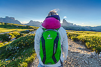A back close-up view of a female athlete as seen on a cold but sunny Summer morning, enjoying the view of Tre Cime di Lavaredo from Monte Piana, South Tyrol, Italy.