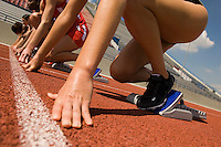 Group of female track athletes on starting blocks