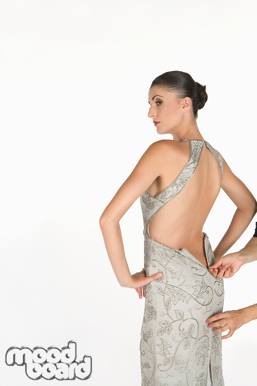 Woman stands waiting for zip to be done up on backless dress