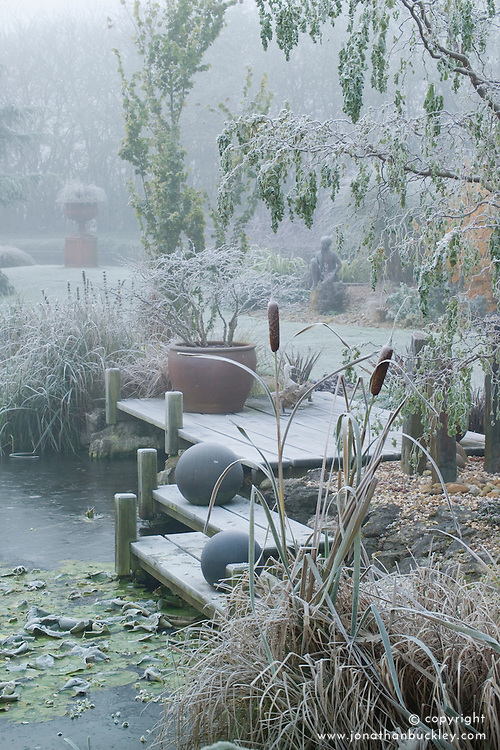 A foggy, frosty morning by the frozen pond in John Massey's garden. Statue, urn and container all acting as focal points. Deck with bronze balls. Bullrushes in the foreground.