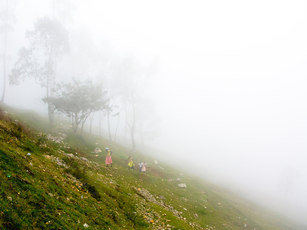 A family walks, in fog, walks up a mountain.