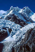 "Glaciers crack and ice falls in a small avalanche from Mount Jirishanca, or the ""Icy Beak of the Hummingbird"" (west face, 6126 m or 20,098 feet elevation), third highest in the Cordillera Huayhuash, tenth highest in Peru. Andes Mountains, South America."