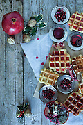 Christmas table with fresh baked waffle and pomegranate sorbet decorated with holly and pomegranate seeds.