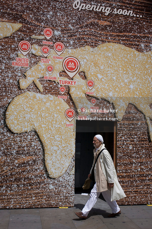 Man walks beneath a world map on a bakery business hoarding.