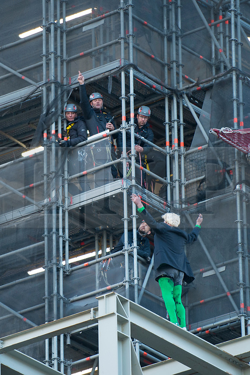 © Licensed to London News Pictures. 18/10/2019. LONDON, UK.  A climate activist (green tights) from Extinction Rebellion gestures to a rescue team after scaling the construction scaffolding of the Queen Elizabeth Tower in Westminster.  Parliament Square and the surrounding area has been brought to a standstill as police and emergency services assess the situation.  Photo credit: Stephen Chung/LNP